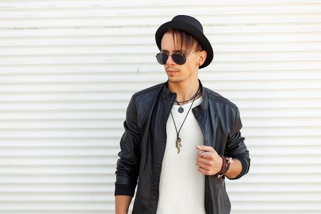 Uomo bello alla moda in vestiti alla moda con occhiali da sole e un cappello vicino al muro di metallo bianco