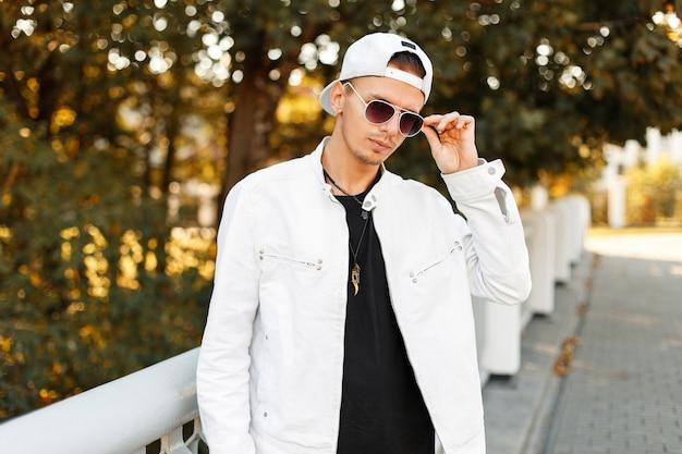 Uomo bello alla moda in occhiali da sole in una giacca bianca con un berretto da baseball per strada in una giornata autunnale