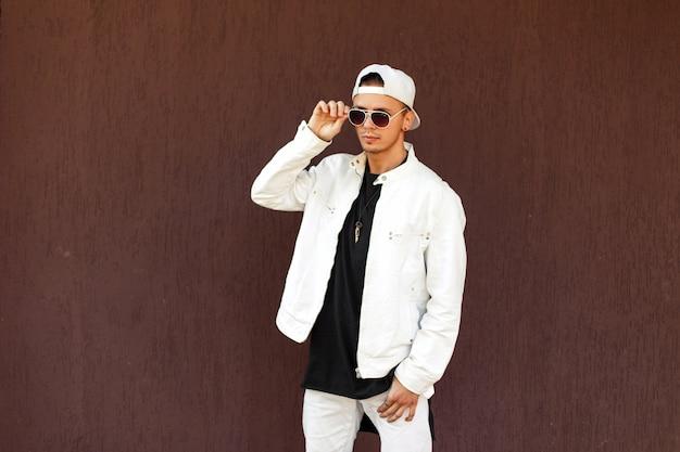 Uomo bello alla moda in una giacca elegante bianca con un berretto da baseball in occhiali da sole in posa vicino al muro