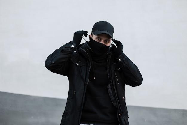 Un bell'uomo alla moda con un berretto nero in una giacca elegante e una felpa con cappuccio indossa una maschera medica protettiva vicino a un muro bianco. stile urbano maschile e concetto di pandemia