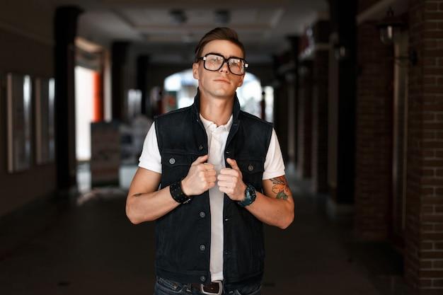 Uomo bello alla moda con gli occhiali in un giubbotto di jeans vicino all'edificio