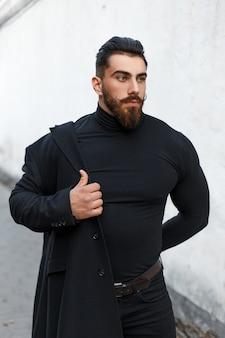Alla moda bell'uomo con una pettinatura e la barba indossa un cappotto elegante nero per strada