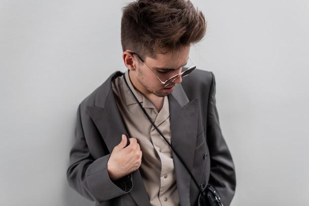 Bell'uomo alla moda con capelli e barba in giacca e camicia alla moda con occhiali da sole su sfondo grigio