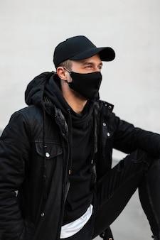 Un bell'uomo alla moda con un elegante berretto nero e una maschera medica protettiva in elegante giacca invernale e felpa con cappuccio si siede all'aperto vicino al muro grigio
