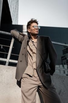 Uomo bello alla moda con occhiali da sole vintage in abito elegante con blazer, camicia e borsetta si trova in città sui raggi del sole. stile maschile elegante e moda casual