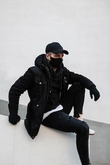 Modello alla moda bel giovane con una maschera protettiva e un berretto nero in un'elegante giacca invernale e una felpa con cappuccio alla moda si siede in città vicino a un muro bianco