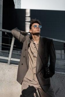 Modello alla moda bel giovane con occhiali da sole in elegante abito grigio con giacca e camicia in città alla luce del sole. stile e successo di affari urbani maschili