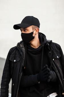 Bel giovane alla moda che indossa un berretto di design mockup nero con una maschera protettiva in una felpa con cappuccio nera con una giacca e guanti per strada