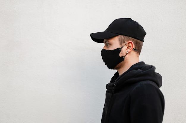 Bel giovane alla moda con una maschera medica protettiva e un berretto nero in un'elegante felpa con cappuccio vicino a un muro bianco con spazio libero per il testo. profilo maschile su sfondo grigio