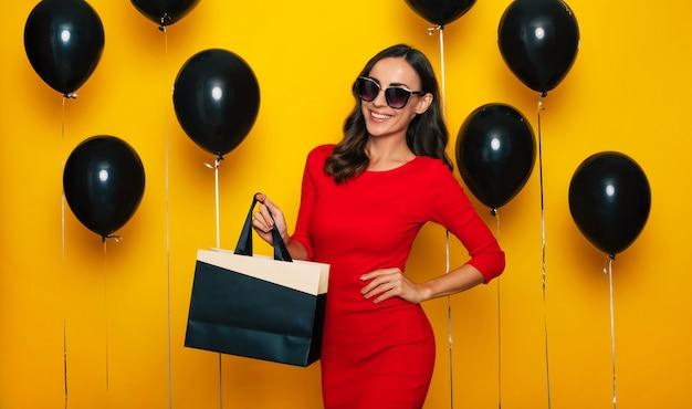 La signora splendida felice alla moda con una borsa della spesa in mano sta posando di buon umore eccitato sullo sfondo di molti palloncini di elio nel venerdì nero