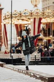 Ragazza sorridente felice alla moda che indossa giacca alla moda di grandi dimensioni, cappello azzurro e sciarpa stanno camminando in strada coperta di neve