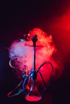 Narghilè alla moda con una nuvola di fumo su uno sfondo nero con bagliore rosso e blu