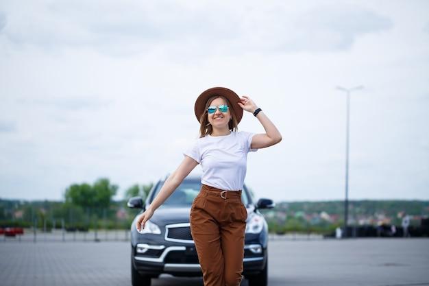 Immagine alla moda di una ragazza alla moda in un cappello e una maglietta bianca. una ragazza è in piedi vicino a un'auto nera con un sorriso sul viso