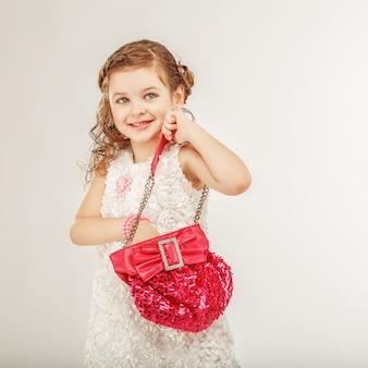 Bambina alla moda che tiene una borsa rosa