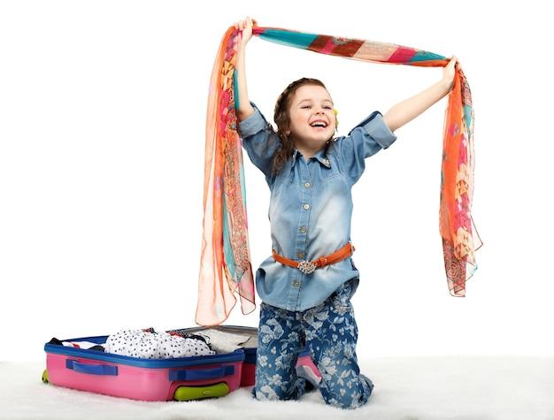 Bambina alla moda che disimballaggio una valigia