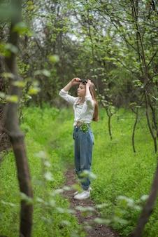 Piccola ragazza teenager alla moda nella foresta, attraverso i rami verdi degli alberi con fieno.