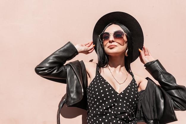 La donna adorabile alla moda in cappello in giacca in vestito in occhiali da sole gode del sole in città. modello attraente della ragazza di modo in bei vestiti neri eleganti di estate che posano alla luce solare intensa vicino alla parete rosa