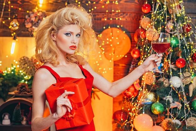 Ragazza di lusso alla moda che celebra il natale o il nuovo anno con vino rosso.