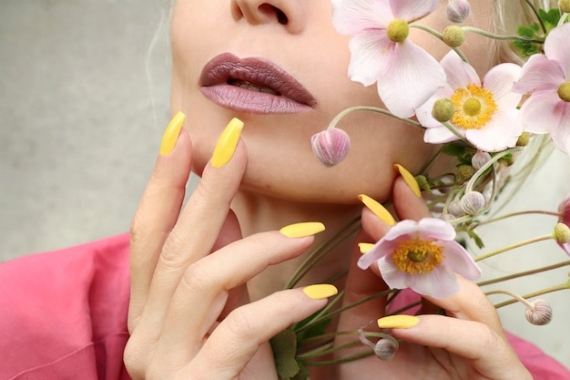 Trucco alla moda e manicure gialla su unghie lunghe