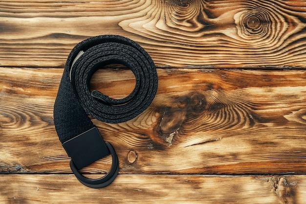 Cintura maschile alla moda su fondo di legno marrone