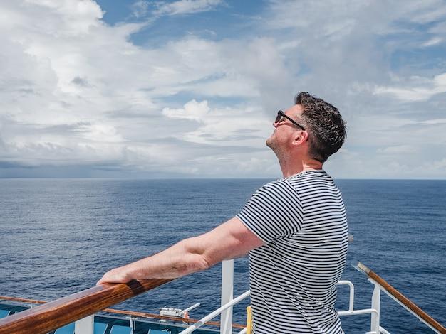 Uomo alla moda sul ponte vuoto di una nave da crociera contro uno sfondo di onde del mare.