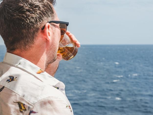 Uomo alla moda che tiene un bel bicchiere