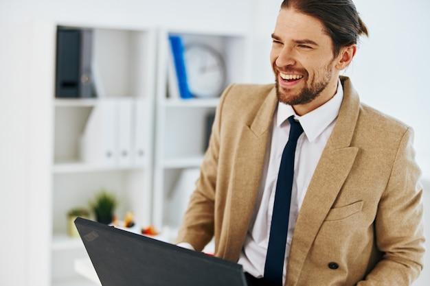 Uomo alla moda in ufficio con tecnologie laptop