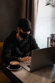 L'uomo alla moda in eleganti abiti neri con un mockup e una maschera protettiva nera è seduto in un bar, beve caffè e lavora al computer portatile