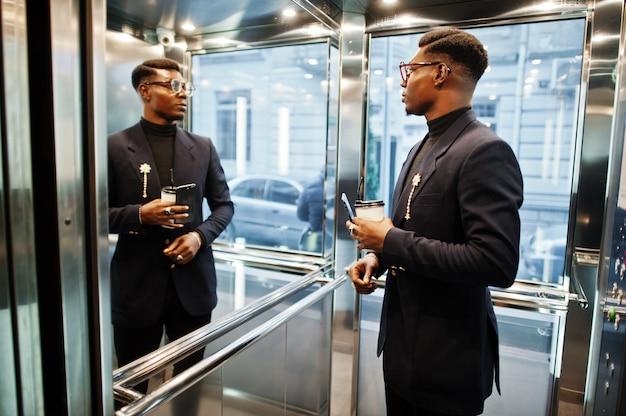 Uomo alla moda in tuta e bicchieri con cellulare e tazza di caffè a mani poste all'interno dell'ascensore