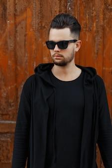 Uomo alla moda in occhiali da sole in una felpa con cappuccio nera vicino a una parete in legno d'epoca