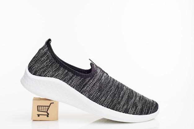 Scarpe da passeggio uomo alla moda con scatola su sfondo bianco. il concetto di acquisto con consegna