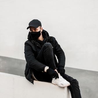 L'uomo alla moda con una maschera medica in eleganti abiti neri con giacca, berretto, felpa con cappuccio e scarpe da ginnastica bianche si siede vicino a un muro bianco in città