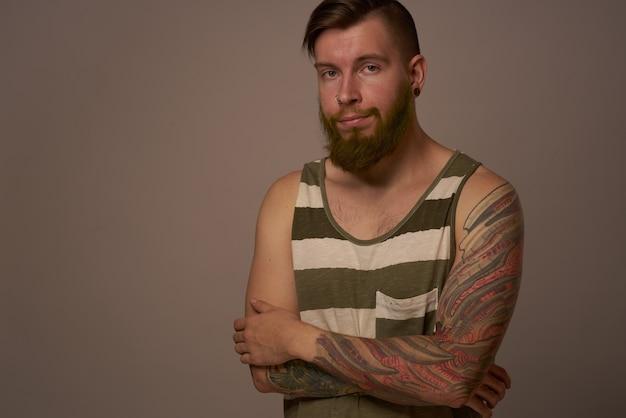 Uomo alla moda con i tatuaggi sulle braccia studio di fiducia in se stessi acconciatura alla moda. foto di alta qualità