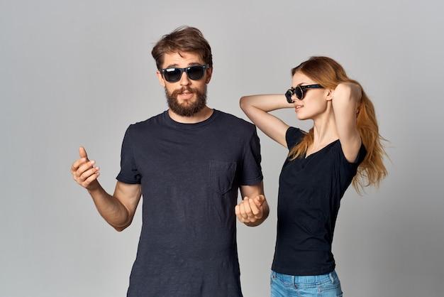 Uomo e donna alla moda in occhiali da sole maglietta nera in posa sfondo isolato