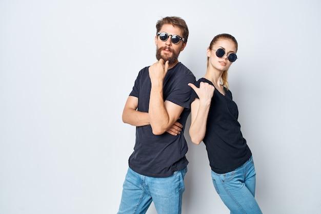 Uomo e donna alla moda amicizia comunicazione romanticismo indossando occhiali da sole sfondo chiaro