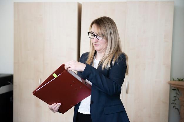 Donna matura alla moda che tiene una cartella rossa con i documenti, lavorando in ufficio