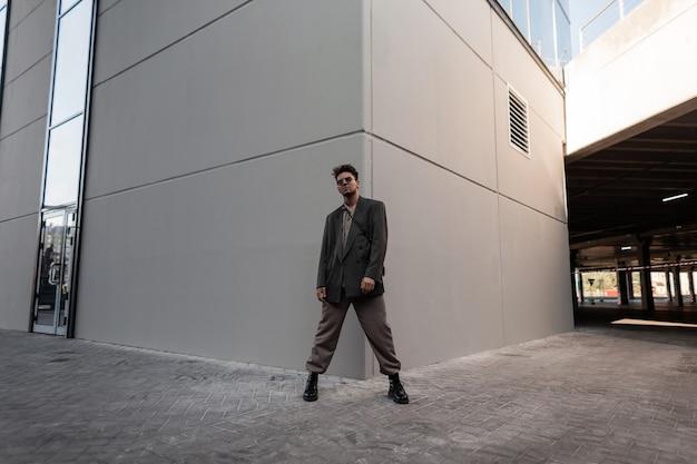 Modello alla moda uomo che indossa abiti eleganti con camicia, blazer, pantaloni e stivali in città. stile urbano e moda maschile