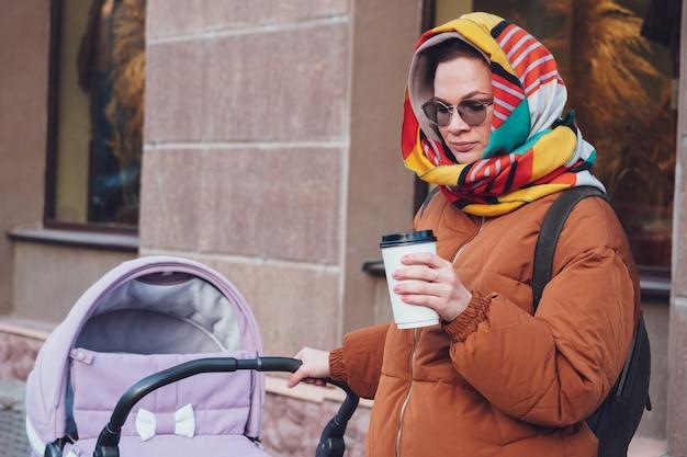 Mamma moderna alla moda con un passeggino in una passeggiata in città, autunno