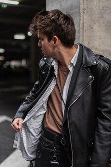 Alla moda e moderno giovane hipster con un'acconciatura alla moda in giacca di pelle oversize alla moda in una camicia distoglie lo sguardo vicino a una colonna vintage in città. modello di ragazzo urbano all'aperto. moda americana.
