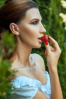 Donna alla moda di passione che mangia fragola dolce rossa. foto primaverile o estiva all'aperto