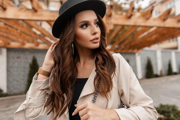 Ritratto alla moda di una bella donna bruna con labbra sexy e capelli ricci in un cappotto beige alla moda con un cappello alla moda cammina per strada. stile femminile elegante e bellezza della natura