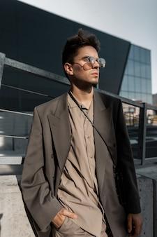 Ritratto alla moda di un bel giovane uomo d'affari professionista con setola con occhiali da sole vintage in abito di moda grigio su sfondo urbano moderno alla luce del sole