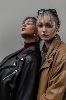 Ritratto alla moda di due belle ragazze con un'elegante giacca di pelle e un maglione lavorato a maglia vicino a un muro grigio in città