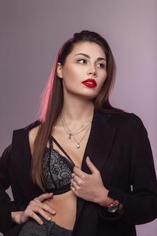 Ritratto alla moda giovane donna con capelli castani con pelle pulita sana con belle labbra rosse gonfie in elegante giacca nera in reggiseno di pizzo in studio. modello di moda ragazza sexy alla moda nella stanza.