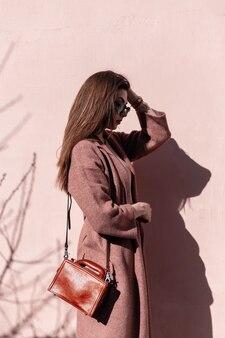 Modello alla moda piuttosto lussuoso della giovane donna in cappotto alla moda con la borsa in occhiali da sole che posano vicino alla parete rosa dell'annata il giorno soleggiato. affascinante ragazza in bei vestiti gode della luce del sole all'aperto.