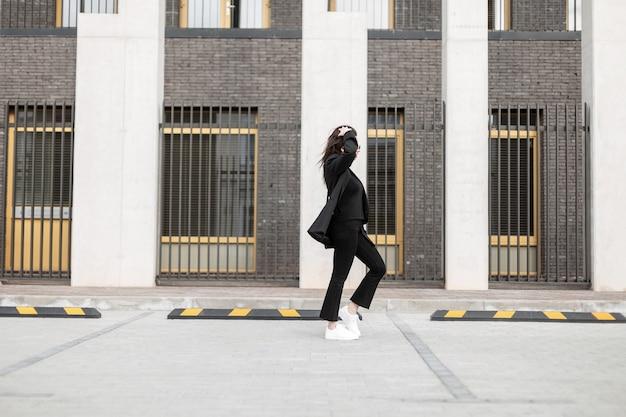 Bella giovane donna alla moda in elegante abito nero in scarpe da ginnastica bianche in pelle alla moda cammina vicino a un edificio moderno in città. la modella urbana della ragazza viaggia per strada. stile giovanile casual. look primaverile