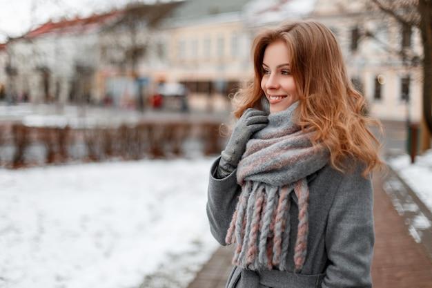 Alla moda bella giovane donna con un bel sorriso in un elegante cappotto grigio in un'elegante sciarpa grigia in guanti in giro per la città vicino a edifici d'epoca