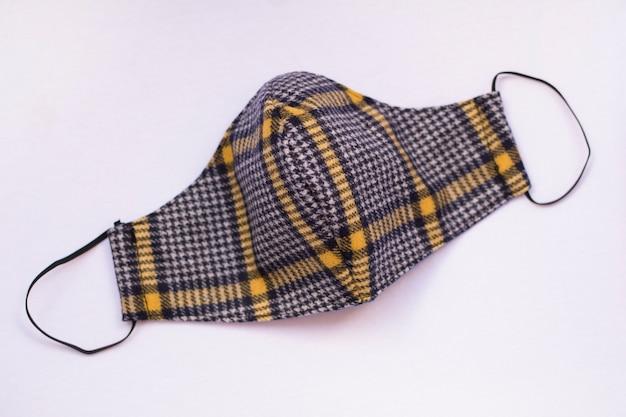 Maschera protettiva alla moda in tessuto scozzese, isolata. protezione pandemica covid-19.