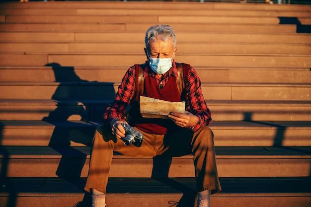 Uomo anziano alla moda che indossa la maschera protettiva e seduto sulle scale.