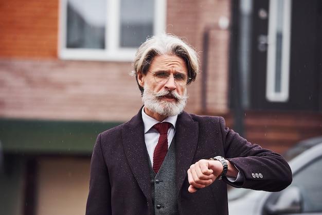 Uomo anziano alla moda con i capelli grigi e la barba è all'aperto per strada vicino alla sua auto che controlla il tempo sul suo orologio.